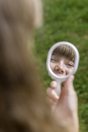 Portrait of young girl looking in the mirror
