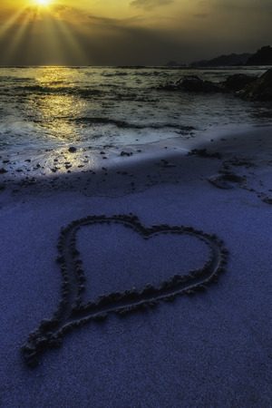 Romantic view of heart shape in sand with sunset background Stock fotó