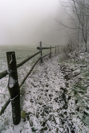 Winter footpath around wooden corral with fog on background