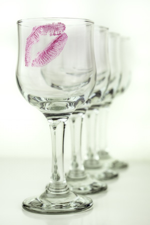 Four glasses on a white background with one kiss on the first glass