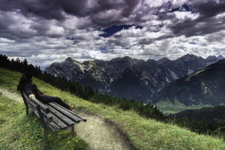 Woman sitting on bench and watching wild on Tyrolean Alps mountains