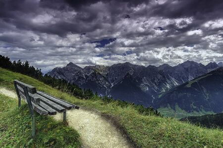 View of bench with mountains on background from Tyrolean Alps in Austria