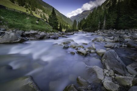 View of the flowing river Ruetz with stones and trees in the background from Stubai  Austria