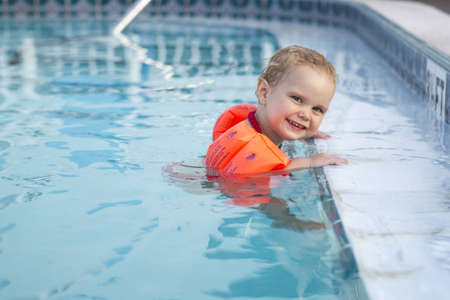 floats: Girl with arm floats holding on to edge of pool Stock Photo