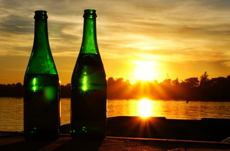 These are two bottles of champagne with sunset in background. Stock Photo - 7365938