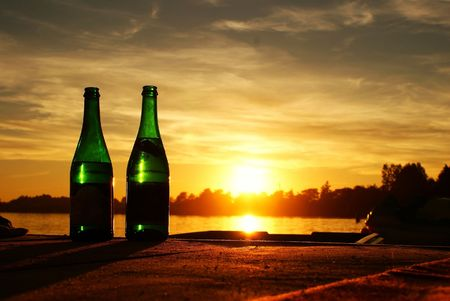 These are two bottles of champagne with sunset in background. photo