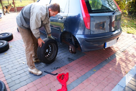 This is a man changing the wheel in the car Stock Photo - 11092664