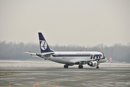 chopin: This is a view of LOT-Polish Airlines plane Embraer ERJ 170 registered as SP-LIK on the Warsaw Chopin Airport. December 31, 2014. Warsaw, Poland.