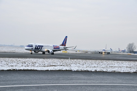 warsaw chopin: This is a view of LOT-Polish Airlines plane Embraer ERJ 170 registered as SP-LIN on the Warsaw Chopin Airport. December 31, 2014. Warsaw, Poland.