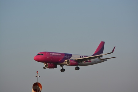 chopin: This is a view of Wizzair plane Airbus A320 registered as HA-LWX landing on the Lublin Airport. February 20, 2015. Lublin Airport in Swidnik, Poland Editorial