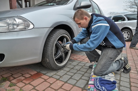 italian car: This is a view of man changing the wheels in Italian car.