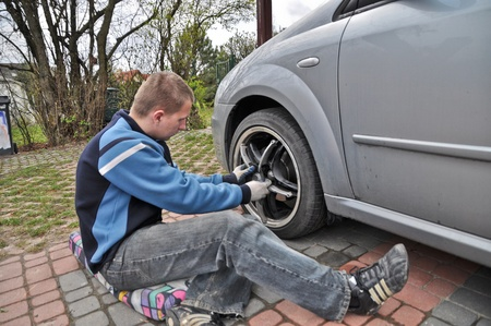 This is a view of man changing the wheels in Italian car. photo