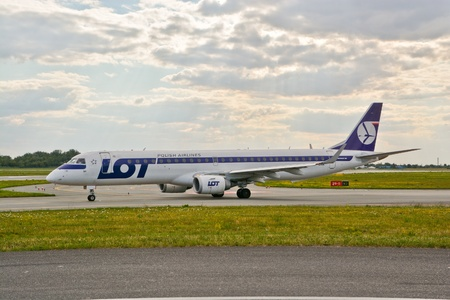 warsaw chopin: This is a view of LOT - Polish Airlines Embraer ERJ 170 plane registered as SP-LNA on the Warsaw Chopin Airport. July 30, 2015. Warsaw, Poland.