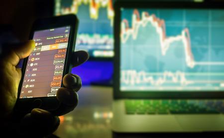 Day trader utilisant un téléphone mobile et des écrans d'ordinateur avec des graphiques, Vienne Autriche, 25-3-2018