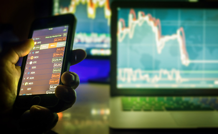 Day trader using mobile phone and computer screens with charts, Vienna Austria, 25-3-2018