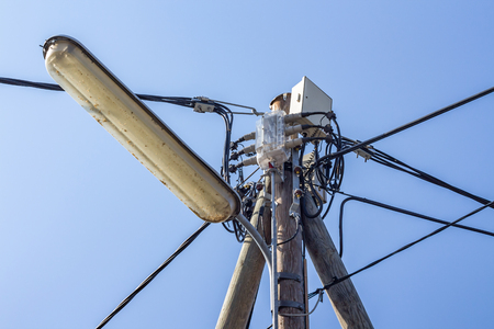 Light pole and various wiring cables against blue sky Stock Photo