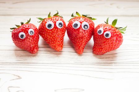 Group of Strawberries with wobbly eyes on wooden backdrop, concept