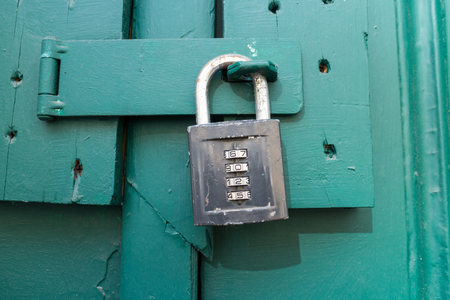 Close up of an old wooden door with numbers combination padlock