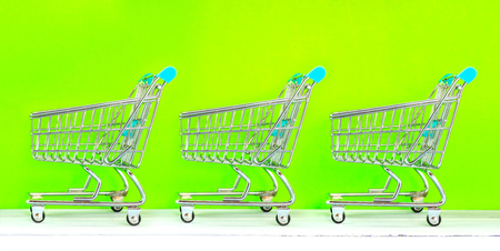 Retail store shopping concept miniature shopping carts on green screen