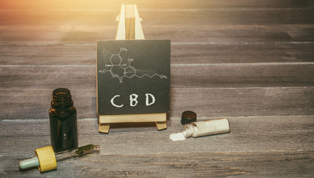 CBD Canabidiol crystals isolate in glass container with CBD chemical formula on chalk board