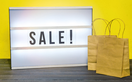 Light box with Sale letters and small shopping bags against yellow background