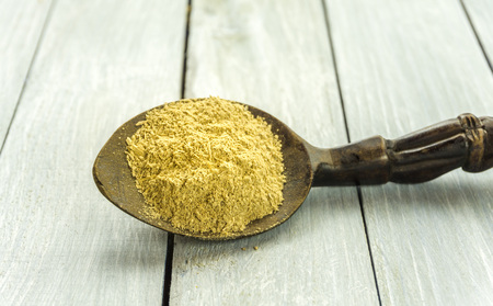 Spoon with Kava Kava root powder on wooden table