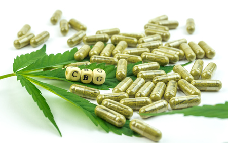 Group of CBG Cannabigerol pills on hemp leaf isolated on white