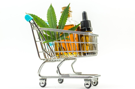 Supermarket trolley with marijuana leafs and medical cannabis oil cbd
