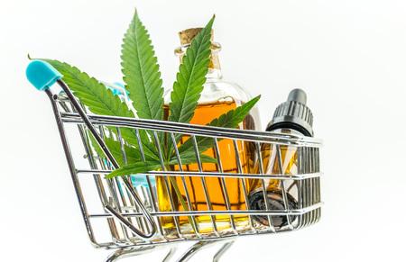 Supermarket trolley with marijuana leafs and medical cannabis oil cbd
