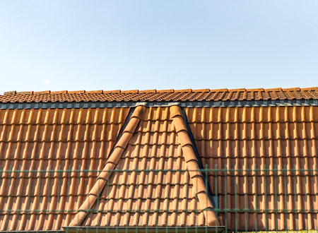Red corrugated tile element of roof at house, Shingles roofing surface tiles overlay pattern against sky
