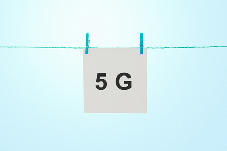 Word 5G on white note paper hanging on rope against sunny blue sky Imagens - 122303279