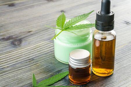 Aceites de CBD de cannabis en botella de vidrio y frascos de gel de loción de CBD con hojas de cáñamo en la mesa de madera