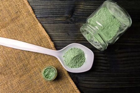Mitragyna speciosa or Kratom powder in ceramic spoon and glass jars on table with hemp cloth