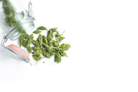 Jar with Medical Marijuana flower buds spill on white background with copy space
