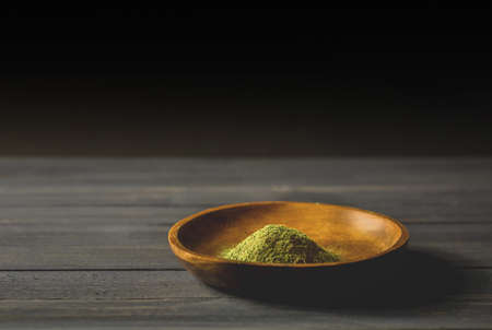 Mitragynina speciosa or Kratom powder in wooden bowl on table, chiaroscuro effect