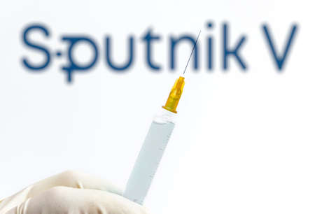 Vienna Austria Jan 29 2021, Syringe against blurred Sputnik V logo, Sputnik is the Russian Covid19 vaccine developed by the Gamaleya Institute