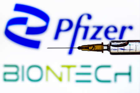 Vienna Austria January 30th 2021, Syringe with liquid back lit by the logos of Pfizer and Biontech, developers of Covid19 vaccine 新聞圖片