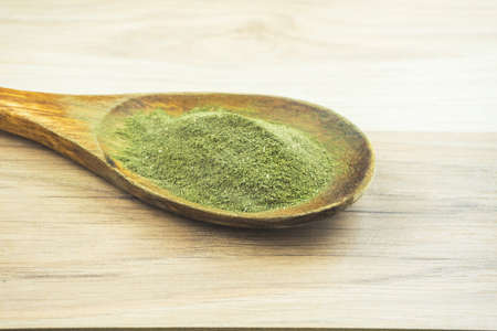 Kava Kava powder in wooden spoon, a natural medicinal plant for relaxation used as a drink
