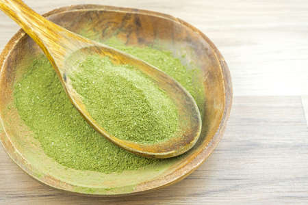 Kratom Mitragyna Speciosa an alternative medicine powder in wooden spoon bowl