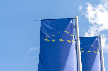 Flags of the European Union on poles against blue sky 版權商用圖片
