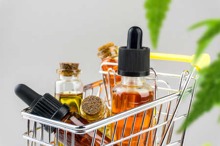 Cannabis CBD oil shopping concept, Medical marijuana oils in miniature shopping cart