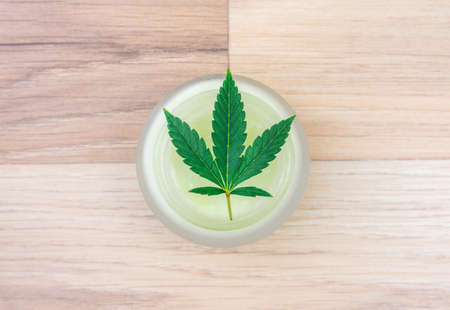 Flat lay of CBD lotion in glass container with Cannabis leaf on wooden backdrop 版權商用圖片