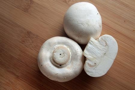 portobello: White champignons, portobello mushroom at the wooden table