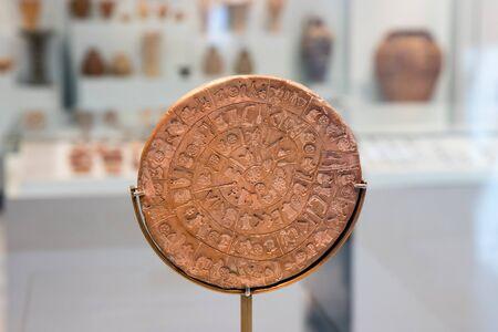 Heraklion, Crete, Greece - 07-01-2017: The Phaistos Disc in Heraklion Archaeological Museum still in exhibition - close up.