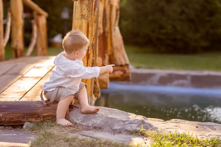 A little boy is sitting on a bridge over a river. He points to the water. Nature walk.