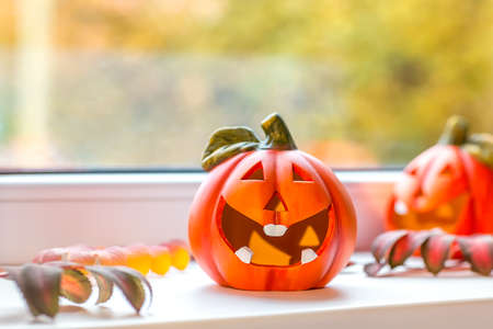 Funny decorative pumpkins for Halloween stand on the windowsill. Outside the window, autumn landscape, bokeh. Selective focus. 版權商用圖片