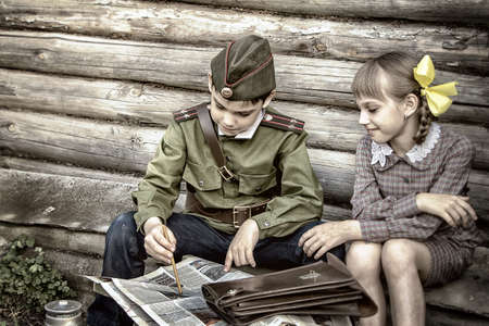 Postcard, stylized as vintage for the Victory Day. A boy in a military uniform and a girl in an old dress. The theme of May 9, Victory Day in Russia. Soft selective focus, added noise.