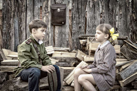 Postcard, stylized as vintage for the Victory Day. A boy in a military uniform and a girl in an old dress are sitting on stumps near a woodpile. The theme of May 9, Victory Day in Russia. Soft selective focus, added noise