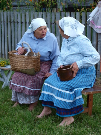 rites: Two senior ladies from the rites team Hansk talking about the customs of the Night of St. John, an old Polish (and Slavic) folk event, June 24th 2011, Open-Air Museum of the Lublin Region Village, Lublin, Poland