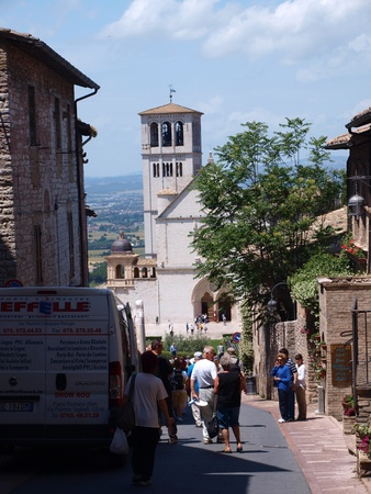 A street in Assisi, Italy leading to the Basilica of Saint Francis of Assisi with crowds of people rushing to the sanctuary.